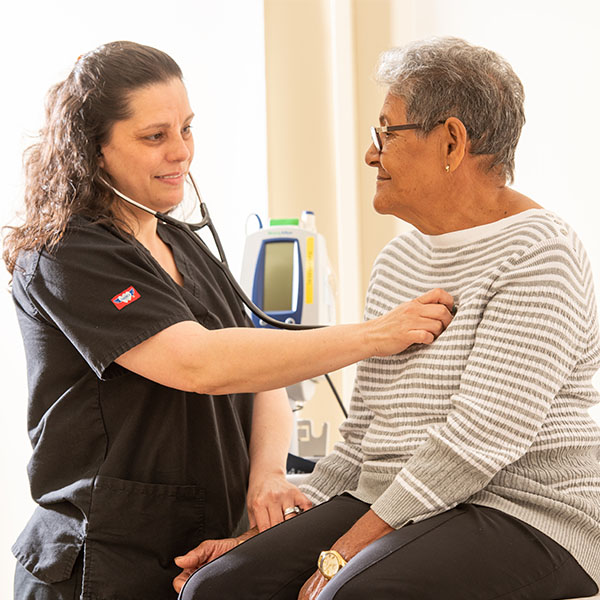 An MA checks the heartbeat of an elderly female patient in the clinic